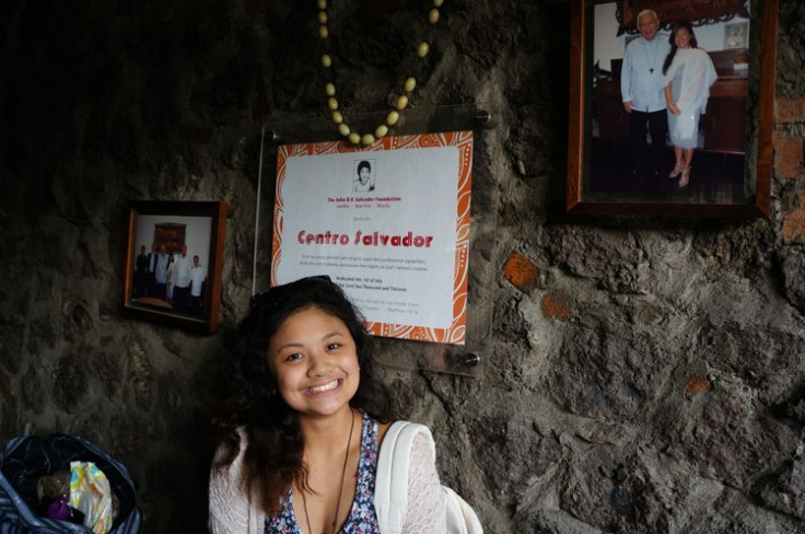 Dana takes a picture in front plaque that thanks her relative Centro Salvador who is the biggest financial donor to this cause